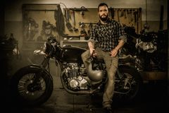 Rider and his vintage style cafe-racer motorcycle Stock Photos