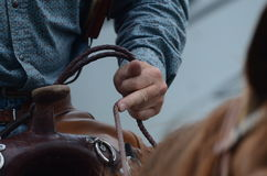 Rider holds onto reins of his horse. A cowboy holds onto his horses reins Royalty Free Stock Photography