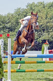 "A rider on a horse.â""–2. Show Jumping - a girl on a horse jumping over the barrier stock image"