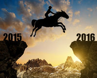 The rider on the horse jumping into the New Year 2016. At sunset Royalty Free Stock Images