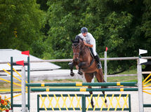 Rider with horse over the hurdle during showjumping competition Stock Photos