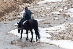 Rider on the horse on the river in winter Royalty Free Stock Photos