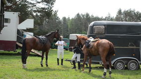 Rider horse walk. People riders prepare horses for steeplechase race on June 01, 2013 in Niuronys, Lithuania stock video