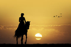 Rider on horseback at sunset Stock Photography