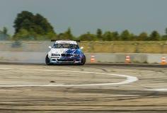Rider Igor Zapisniy en la marca BMW del coche supera la pista Fotos de archivo libres de regalías