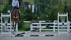 The rider jump over the barrier at the arena stock footage