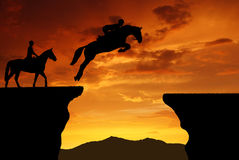 Rider on a jumping horse. Silhouette of a rider on a jumping horse in the sunset Royalty Free Stock Photography