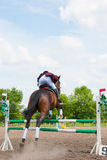 Rider jumping over the barrier Stock Photo