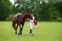 Rider leads horse by bridle Royalty Free Stock Photos