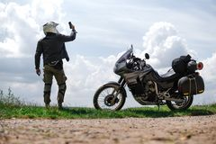 Rider Man holds a smartphone, lost the signal, coverage of mobile communication, off road adventure motorcycles with side bags and stock images
