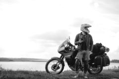 Rider Man and off road adventure motorcycles with side bags and equipment for long road trip, river and clouds on background, royalty free stock images