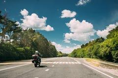 Rider On Motorbike, Motorcycle Bike In Motion On Country Road. Motion On Freeway In Europe. Asphalt Motorway, Highway Through Fields Eastern European Landscape royalty free stock photo