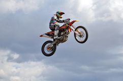 A rider by motorcycle MX flies. Motocross, a rider by motorcycle MX flies over the hill against the blue sky stock photography