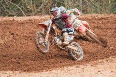Rider Pops Wheelie Accelerating Through Muddy Turn In Motocross Race Royalty-vrije Stock Fotografie