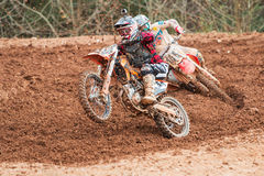 Rider Pops Wheelie Accelerating Through Muddy Turn In Motocross Race. Monroe, GA, USA - December 3, 2016:  A rider pops a wheelie while accelerating out of a Royalty Free Stock Photography