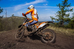 Rider rides on mountain, dirt and stones from under wheels Stock Images