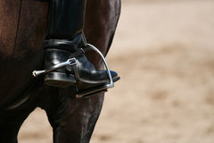 Rider's boot with spur. Rider's black boot with spur in stirrup stock images