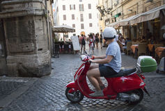 Rider on Scooter. A Rider with helmet on a red scooter in the cobbled streets of Rome, Italy, Tourist, Attraction Royalty Free Stock Photography