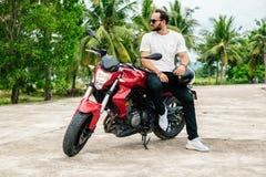 Rider sitting on his motorbike on palm background