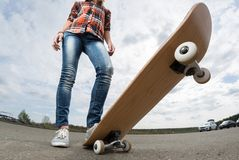 Rider with the skateboard. Rider standing on the asphalt road with the skateboard Stock Images