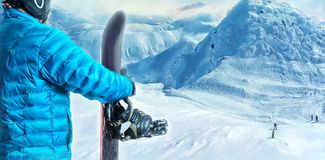 Rider with snowboard standing in the mountains Royalty Free Stock Photo