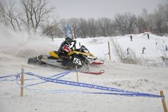 Rider snowmobile accelerates from the sharp turn Royalty Free Stock Photos