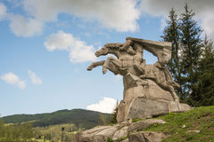 Rider on a stallion statue on a hill. A large stone statue of a rider on a galloping horse stands on a green hill in rural Bulgaria Royalty Free Stock Images