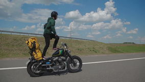 Rider stands on a motorcycle on stock video footage