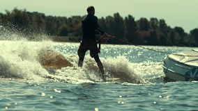 Rider wake boarding boat. Sportsman enjoy summer extreme. Man wake surfing on river. Water extreme lifestyle. Young man riding wake surf on city lake. Man stock footage