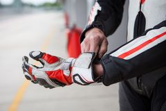 The rider wears the glove. Motorcycle racer puts on a glove before the competition, sports equipment close-up royalty free stock photo