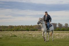 A fermer on a white horse in the field. A rider on a white horse in the field stock photos