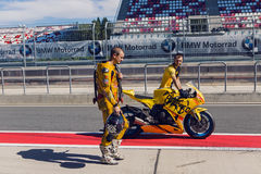 Rider yellow suit and helmet, and technical personnel to carry the bike around the pits after the race Stock Photography