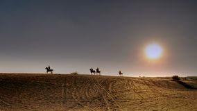 Riders on Arabian horses gallop across the desert at sunset. Riders on Arabian horses gallop across the desert dunes on the outskirts of Dubai, as the sun sets Royalty Free Stock Photography