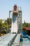 Riders in boat on water slide attraction Stock Photos