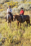 Riders in the Brush. Experienced cowboys riding their horses in the desert royalty free stock photos