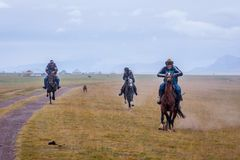 Riders galloping in rain, Kyrgyzstan Stock Photography