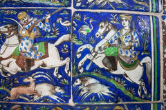 Riders on horseback during the hunt on the vintage colorful ceramic tiles, preserved since the 19th century in Iran Stock Image