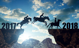 The riders on the horses jumping into the New Year 2018. At sunset Stock Image
