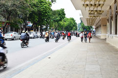 Riders ride motorbikes on busy road, Hanoi Stock Photos