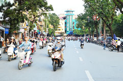Riders ride motorbikes on busy road, Hanoi Stock Photo