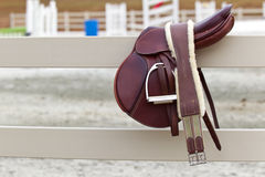 Riders Saddle. A dark english saddle sits on a fence with jumps in the background royalty free stock images