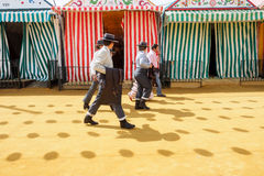 Riders walk through the April Fair Seville dressed in tradional traje corto Royalty Free Stock Image