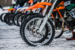 Riders and wheels of motorcycles on starting line Stock Photos