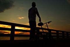 Rides bicycle on the bridge Stock Images
