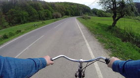 Rides a bicycle on a country road stock footage