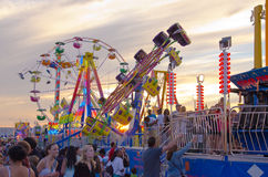 Rides at Sunset. People walking amidst amusement park rides at sunset Royalty Free Stock Images