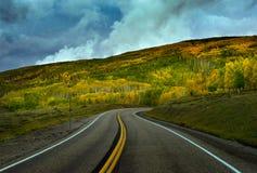 Ridge della tremula di autunno oltre la strada curva sotto il cielo nuvoloso immagini stock
