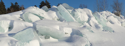 Ridge of ice boulders on a forest background. Royalty Free Stock Images