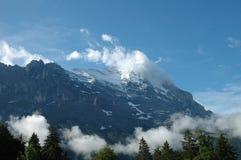Ridge och Eiger når en höjdpunkt i moln närliggande Grindelwald i Schweiz Fotografering för Bildbyråer