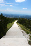 Ridge sidewalk with steps in National Park. Ridge sidewalk with steps in Lovcen National Park, Montenegro. Small trees on both sides of the path and rough Stock Image